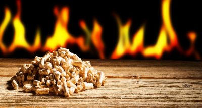 Renewable or sustainable energy concept with a row of burning flames behind a heap of natural wood pellets in a panorama view with copy space